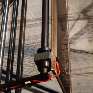 new silk ribbon warp knotted-in and weaving through the back reed of the jacquard loom