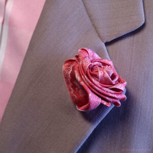Silk Boutonnière. Very Papilionaceous Petal Pin styled from our own rose pink jacquard silk ribbon mounted on a Sterling Silver stick pin worn on a pure wool wedding suit by Nicole Farhi.