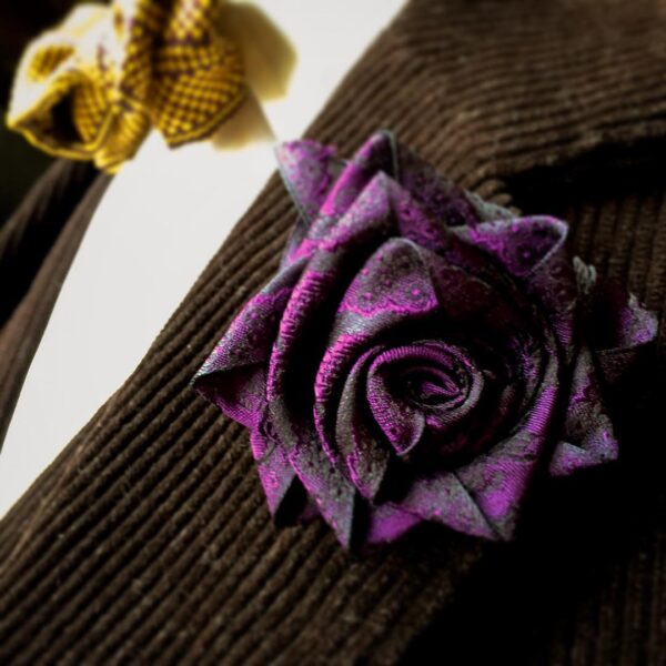 Papilionaceous Petal Pin styled from our own rose pink jacquard silk ribbon mounted on a Sterling Silver stick pin. Made from Papiluionaceous jacquard silk ribbon on chocolate brown 3 piece cord suit by Mr Eddie..